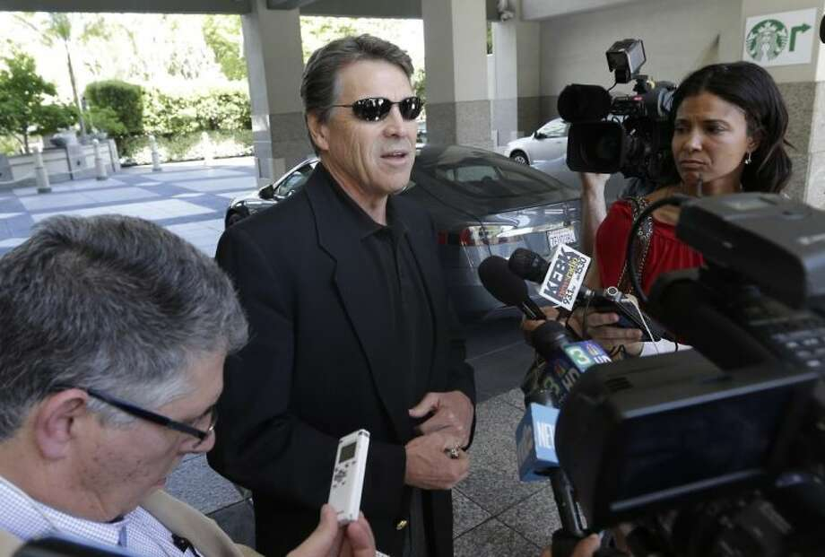 In this June 10 photo, Texas Gov. Rick Perry, center, talks to reporters after driving up in a Tesla Motors Type S electric car in Sacramento, Calif. On Thursday, Perry said it was a mistake for him to recently compare alcoholism and homosexuality in an effort to explain his views.