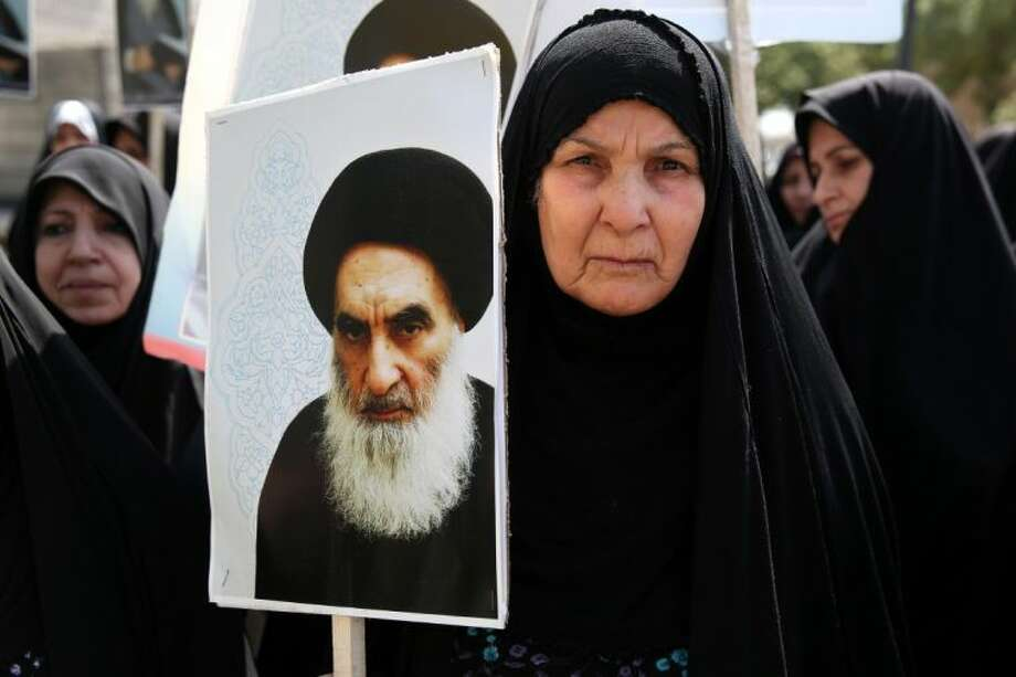 An Iraqi woman living in Iran holds a poster of the Grand Ayatollah Ali al-Sistani, Iraq's top Shiite cleric, in a demonstration against Sunni militants of the al-Qaida-inspired Islamic State of Iraq and the Levant, or ISIL, and to support Ayatollah al-Sistani, in Tehran, Iran.