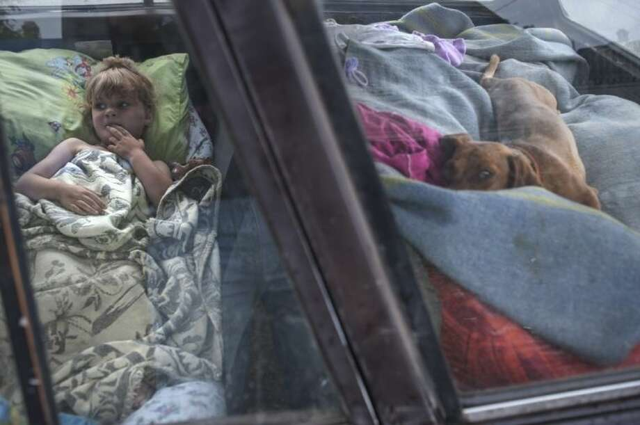 A child and a dog lie in a car standing in line to cross the border into Russia at the Ukrainian-Russian border checkpoint in Izvaryne, eastern Ukraine, Friday.