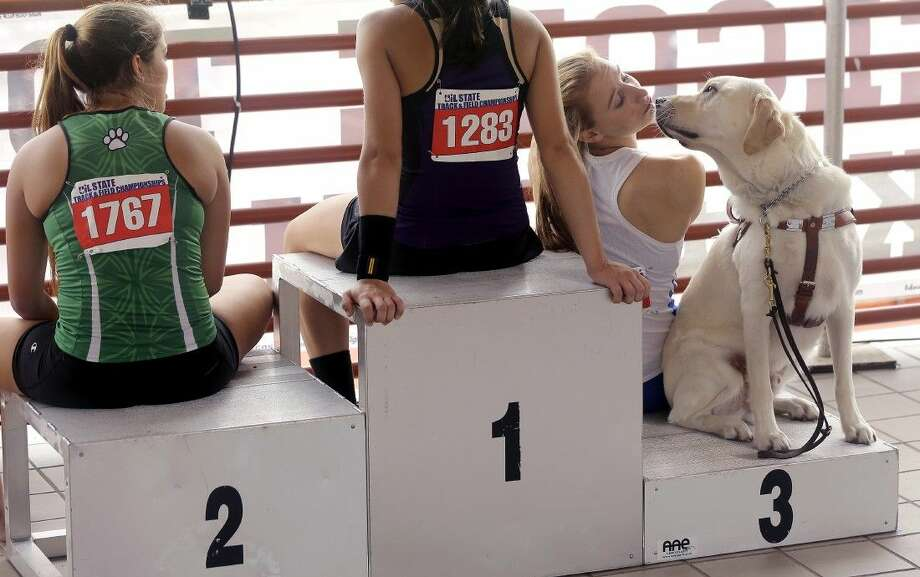 Emory Rains' Charlotte Brown, right, who is legally blind, sits with her guide dog, Vader, as she waits to receive her award after competing in the Conference 4A girls pole vault event at the UIL Texas State Track and Field Championships, Saturday in Austin, Texas. Brown won a Bronze medal with her third place finish. Photo: Eric Gay