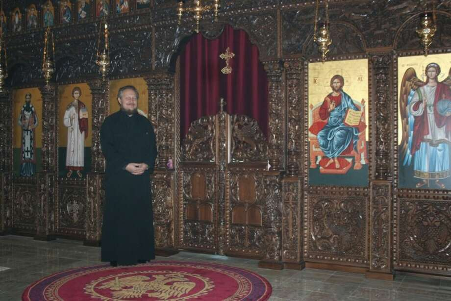 Photo by REBECCA BENNETT/The MirrorFather Dejan Tiosavljevic, the parish priest of St. Sava Serbian Orthodox Church in Cypress, stands before the church's iconostasis, which was handmade by monks in Mount Athos, Greece.