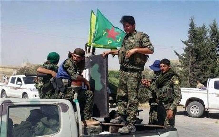 In this photo provided by the Kurdish fighters of the People's Protection Units (YPG), which has been authenticated based on its contents and other AP reporting, Kurdish fighters of the YPG, sit on their pickup in the town of Ein Eissa, north of Raqqa city, Syria, Tuesday. Kurdish fighters and their allies have captured an Islamic State group military base in northern Syria under the cover of U.S.-led airstrikes bringing them closer than ever to the extremists de facto capital of Raqqa, activists said Tuesday. Photo: Uncredited