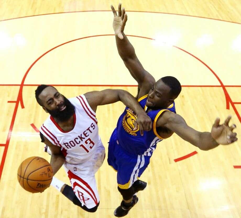 Houston Rockets guard James Harden, left, shoots against Golden State Warriors forward Draymond Green. Photo: Ronald Martinez