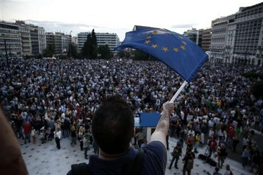 A pro-euro protester waves a European Union flag from the parliament during a rally in Athens, on Thursday. More than 5,000 people attended the rally in support of Greece remaining in the euro. About three-quarters of Greeks support keeping the EU's common currency, according to recent polls. Greece and creditors failed to reach an agreement Thursday in troubled bailout talks, with a June 30 deadline looming. Photo: Yorgos Karahalis