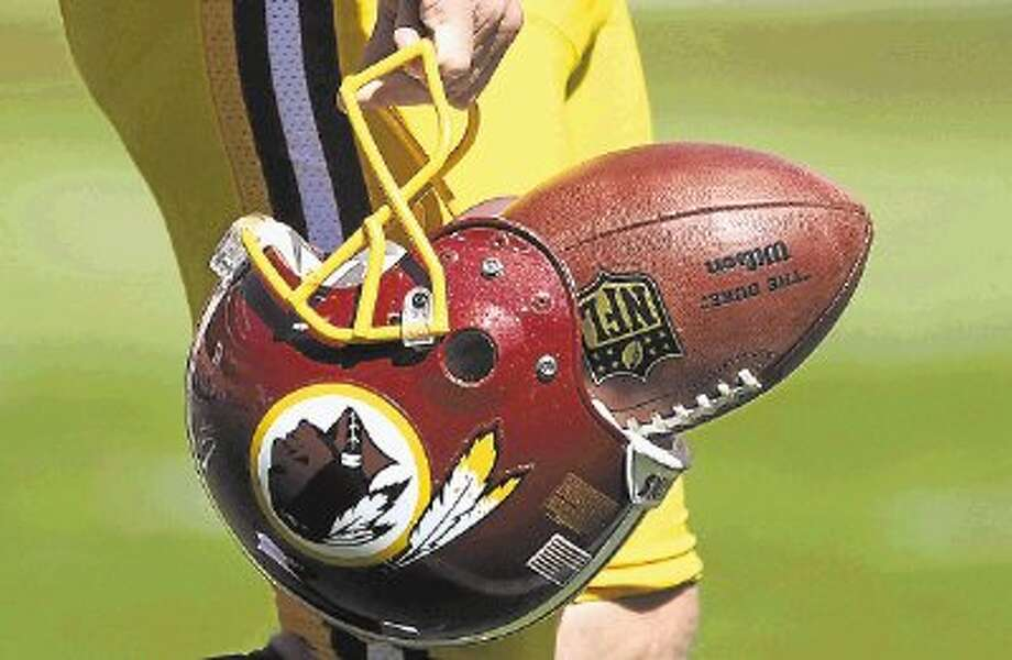 "FILE - In this Sept. 23, 2012, file photo, Washington Redskins punter Sav Rocca carries a football in his helmet before an NFL football game against the Cincinnati Bengals in Landover, Md. The U.S. Patent Office ruled Wednesday, June 18, 2014, that the Washington Redskins nickname is ""disparaging of Native Americans"" and that the team's federal trademarks for the name must be canceled. The ruling comes after a campaign to change the name has gained momentum over the past year. (AP Photo/Nick Wass, File) Photo: Nick Wass / @WireImgId=2680595"
