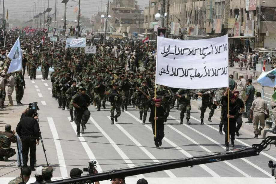"""Volunteers of the newly formed """"Peace Brigades"""" participate in a parade in the Shiite stronghold of Sadr City, Baghdad, Iraq, Saturday."""