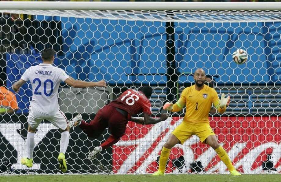 Portugal's Silvestre Varela, middle, sends a header past U.S. goalkeeper Tim Howard in the final seconds, giving his team a 2-2 draw in the final seconds of their World Cup match. Photo: Martin Mejia