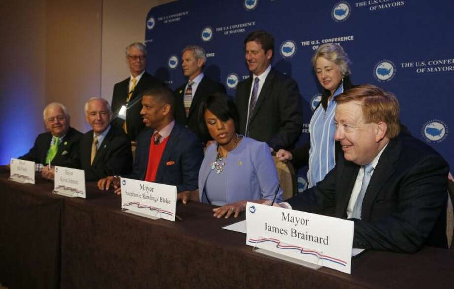 """From front left; Tom Cochran, CEO of The United States Conference of Mayors, Bridgeport Mayor Bill Fitch, Sacramento Mayor Kevin Johnson, Baltimore Mayor Stephanie Rawlings-Blake and Carmel, Ind. Mayor James Brainard sign The U.S. Mayors Climate Protection Agreement at the U.S. Conference of Mayors at the Omni Hotel in Dallas, on Sunday, June 22, 2014. The resolution encourages cities to use natural solutions to """"protect freshwater supplies, defend the nation's coastlines, maintain a healthy tree cover and protect air quality,"""" sometimes by partnering with nonprofit organizations. Photo: Michael Ainsworth"""