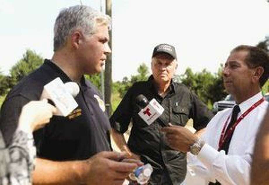 Montgomery County District Attorney Brett Ligon speaks with the media as County Attorney J D Lambright looks on at a Conroe horse-breeding site Wednesday. Photo: Jason Fochtman