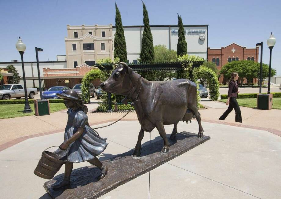 A woman walks by the Blue Bell Creameries on Tuesday in Brenham. Photo: Brett Coomer