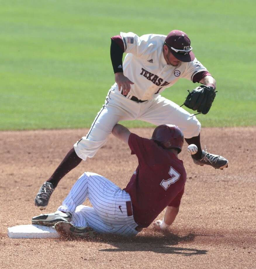 Alabama's Casey Hughston, right, slides safely into second base as Texas A&M's Blake Allemand drops the ball. Photo: Butch Dill