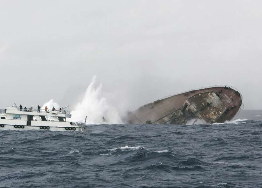 In this November 17, 2007 photo provided by the Texas Parks and Wildlife Department, spectators watch as the Texas Clipper goes under in a controlled sinking near South Padre Island, Texas. Texas Parks and Wildlife Department officials are looking for a ship to buy and sink in the Gulf of Mexico for another artificial reef. Photo: EARL NOTTINGHAM