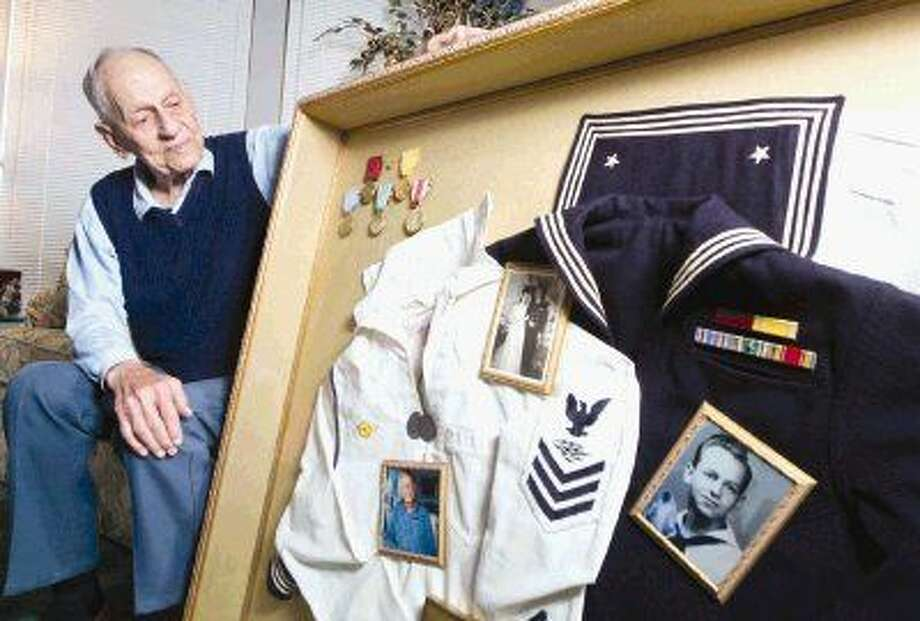 World War II veteran Nick Stine looks over his Navy uniforms at his home in Montgomery. Stine was a sonar operator and gunman during his service that included action at the Battle of Normandy and the Atlantic. Photo: Jason Fochtman