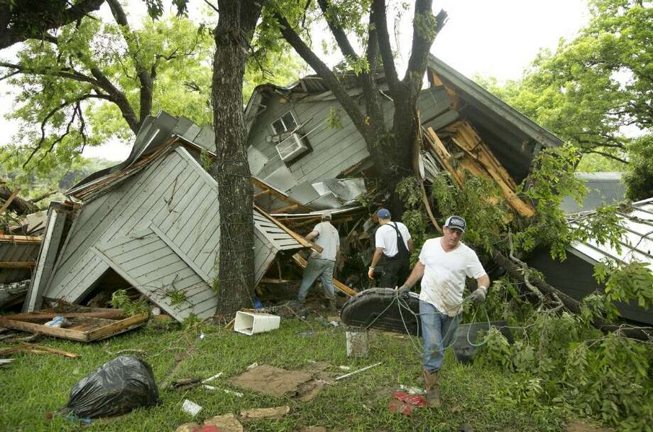 Jeremy Steele, left, Ric Jaime, center, and Keith McNabb salvage belongings at their friend Mike Cook's house near Wimberley, Texas, Sunday. About 350 homes in the town of Wimberley were washed away by flash floods along the Blanco River, which rose 26 feet in just one hour and left piles of wreckage 20 feet high, Texas authorities said. Photo: Jay Janner
