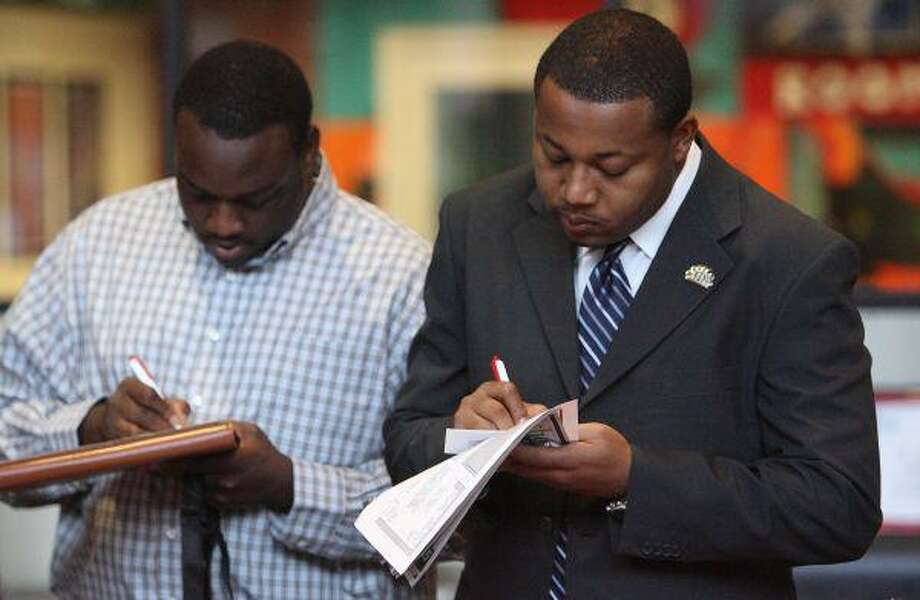 Job seekers fill out applications in front of booth of one of more than 25 employers present at the South Montgomery County Woodlands Chamber of Commerce 2010 Community Job Fair Thursday at Lone Star College-Montgomery in The Woodlands. / The Courier