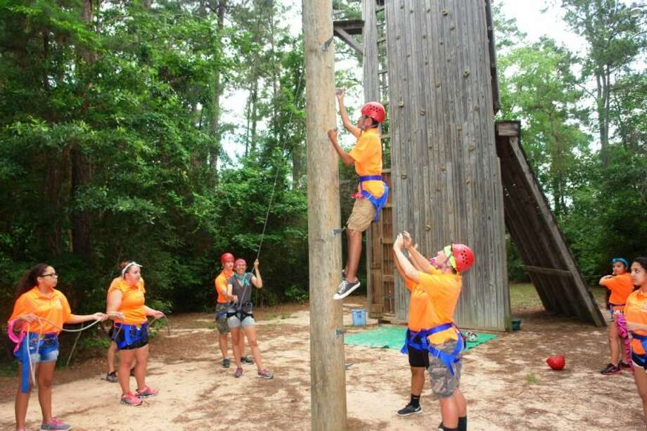 Conroe ISD seniors attend a Kid Chat Leadership camp last week as part of their training in the Junior Leadership Program. Students learn to be crime fighters with CISD's Kid Chat program. Pictured above is Baldemar Esquivel, climbing high with the support of his classmates.