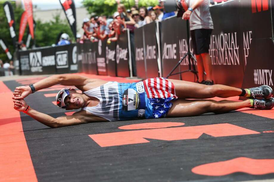 Matt Russell, of Ogdensburg, NY., rolls on the ground, in honor of his mother and others who have suffered from ALS, after placing second in the Memorial Hermann Ironman North American Championship on Saturday in The Woodlands. To view more photos from the event, go to HCNPics.com. Photo: Michael Minasi