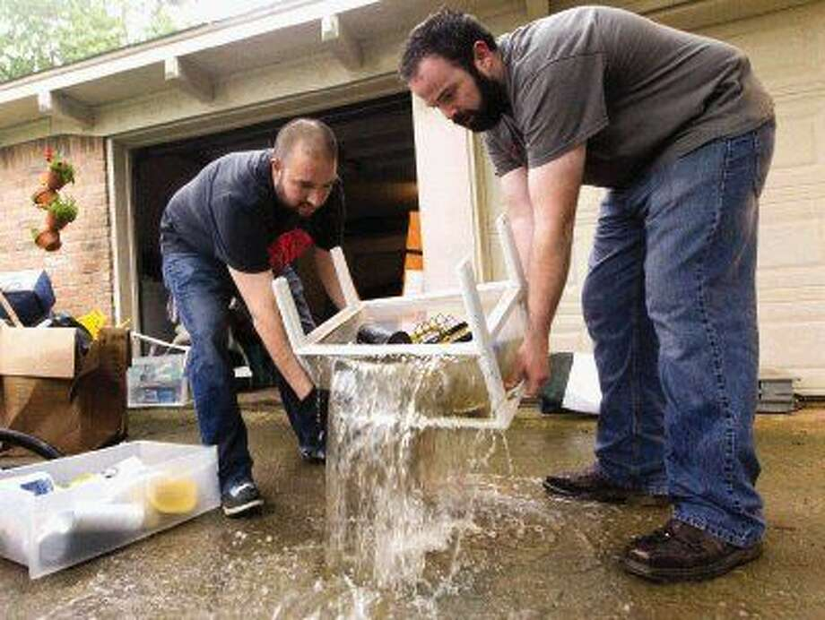 Evan Gooch, right, helps Noe Ortiz dump flood-water out of a shelf at a friend's home in the Timber Ridge Timber Lakes subdivision Thursday. Photo: Jason Fochtman
