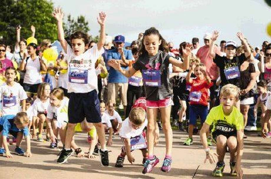 Runners warm up with some exercises before the inaugural Children's Memorial Hermann Ironkids Texas Fun Run on Saturday at Town Green Park. Photo: Michael Minasi