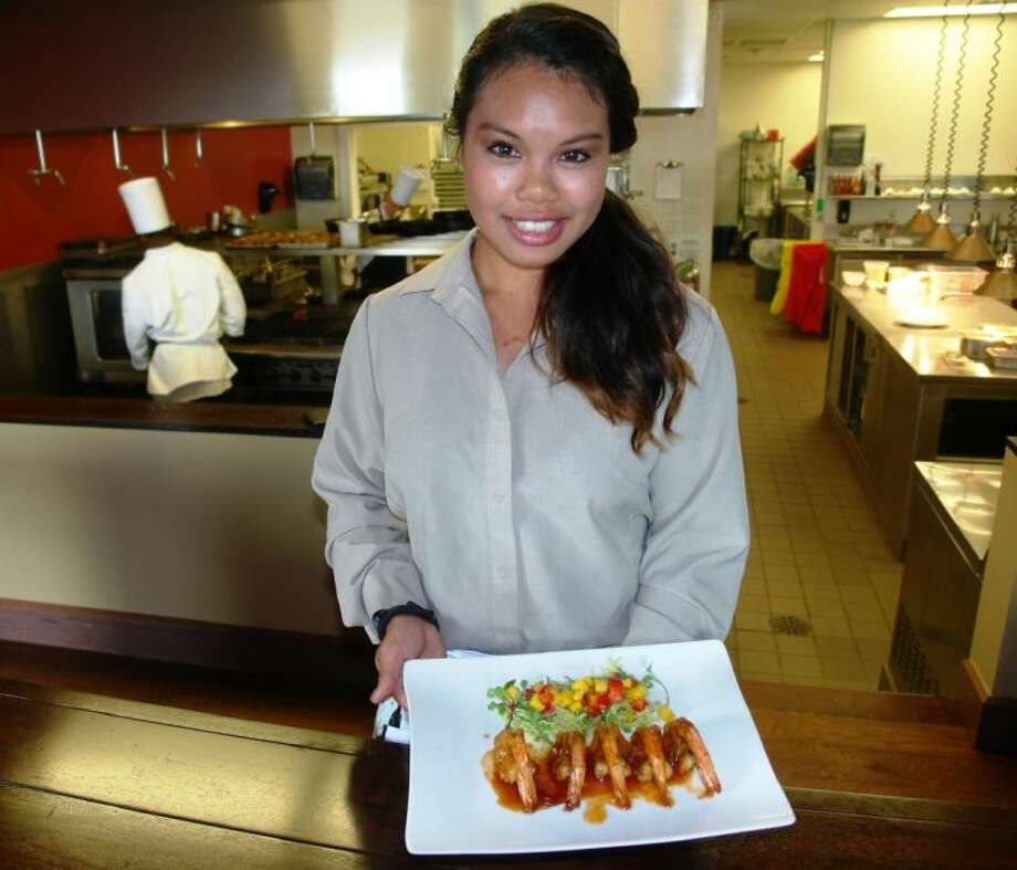 Ashley Ha, a server at Lakeside Restaurant at La Torretta Resort and Spa serves Sauteed Gulf Shrimp with a sweet chipotle lime glaze and mango salsa on the side.