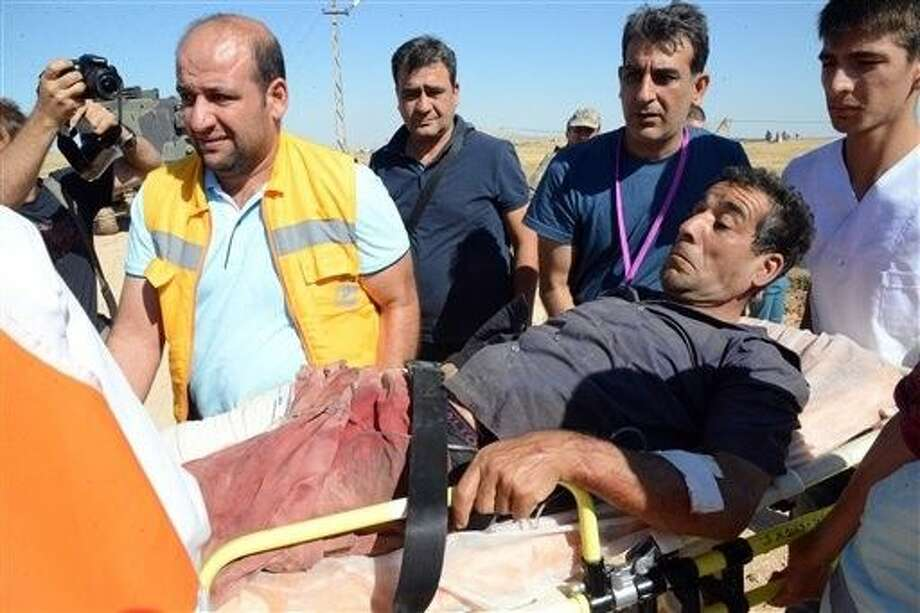 Turkish medics carry a wounded person arrived from the Syrian town of Ayn al-Arab or Kobani following the attacks by IS militants, on the Turkish side of the border in Suruc, Turkey, Thursday. Photo: STR