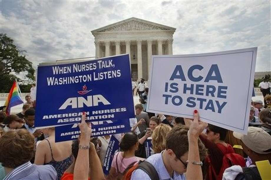 Supporters of the Affordable Care Act hold up signs as the opinion for health care is reported outside of the Supreme Court in Washington, Thursday. Photo: Jacquelyn Martin