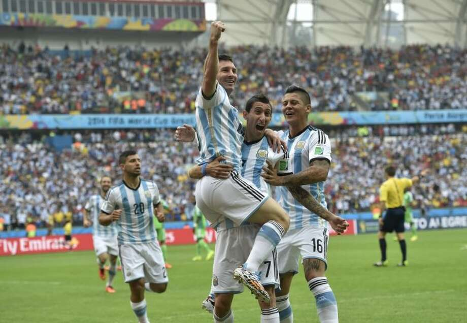 Argentina's Lionel Messi, left, celebrates with teammates Ángel di María and Marcos Rojo (16) after scoring in the third minute during a Group F World Cup match against Nigeria on Wednesday at Estádio Beira-Rio in Porto Alegre, Brazil. Photo: Martin Meissner