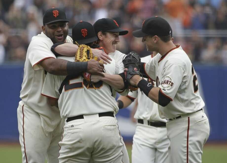 San Francisco Giants players, from left, Pablo Sandoval, Hector Sanchez and Buster Posey swarm pitcher Tim Lincecum after his no-hitter against the San Diego Padres on Wednesday in San Francisco. Photo: Eric Risberg