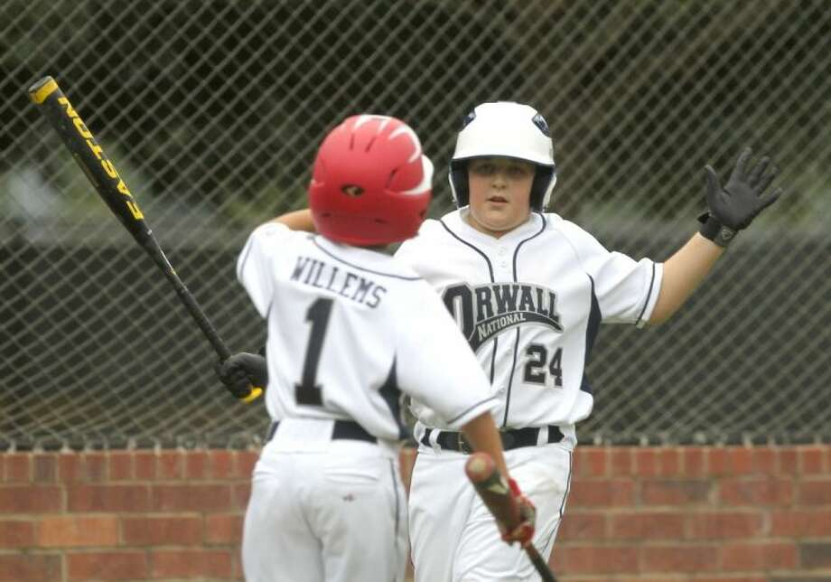ORWALL National League's Jaiden Willems (1) gets a high-five from teammate Colin West after scoring a run in the first inning during the opening the round of the 10- and 11-year-old District 28 tournament on Wednesday at the ORWALL fields in Spring. To view or purchase this photo and others like it, visit HCNpics.com. Photo: Jason Fochtman