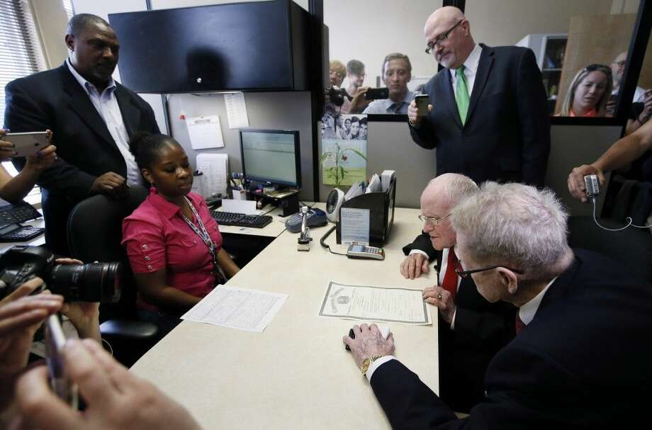 Dallas County Clerk John Warren, standing left, watches as George Harris, seated right background, and Jake Evans, right foreground, verify their information on the first same sex marriage license issued by Dallas county in Dallas on Friday. Photo: Tony Gutierrez