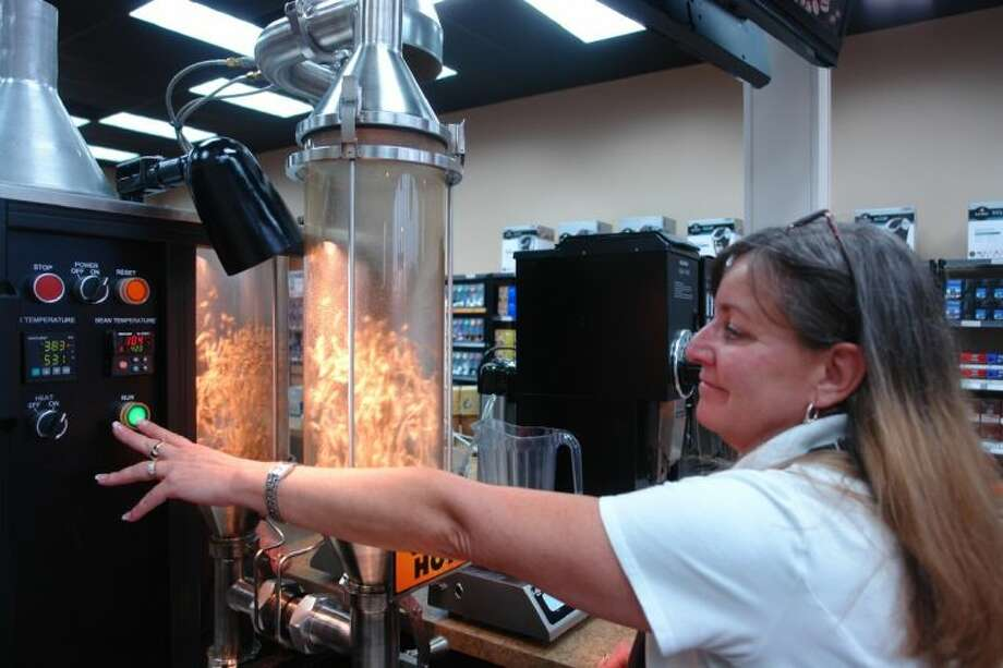 Lisa Knight, manager of CoffeeIcon in Magnolia, roasts coffee beans for a customer. The store offers hundreds of varieties of coffee from all over the world as well as specialty and novelty items.