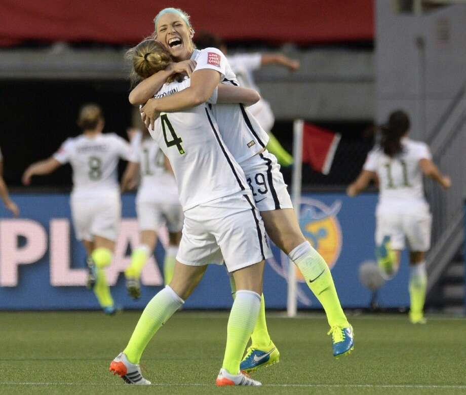 United States' Julie Johnston (19) and Becky Sauerbrunn (4) celebrate a goal against China by Carli Lloyd during the second half of a quarterfinal match in the FIFA Women's World Cup, Friday in Ottawa, Ontario, Canada. Photo: Adrian Wyld
