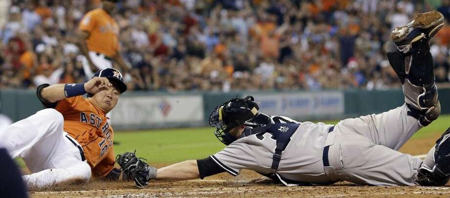 Houston Astros' Hank Conger (16) slides safely across home plate as New York Yankees catcher Brian McCann reaches to tag him during the third inning Friday. Photo: David J. Phillip