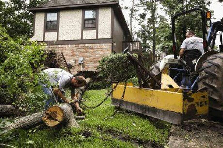 Employees of Dangerous Tree Removal attach a chain to a downed tree on the front lawn of a home that was caught in the path of a tornado on Sunday morning along Timberjack Place in The Woodlands. Photo: Michael Minasi