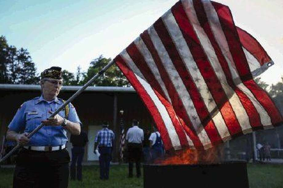 Sheila Schulte, commander of the American Legion Honor Guard, retires a flag in a formal ceremony during Flag Day on Sunday at the American Legion Post 618 in Willis. To view or purchase this photo and others like it, visit HCNpics.com. Photo: Michael Minasi