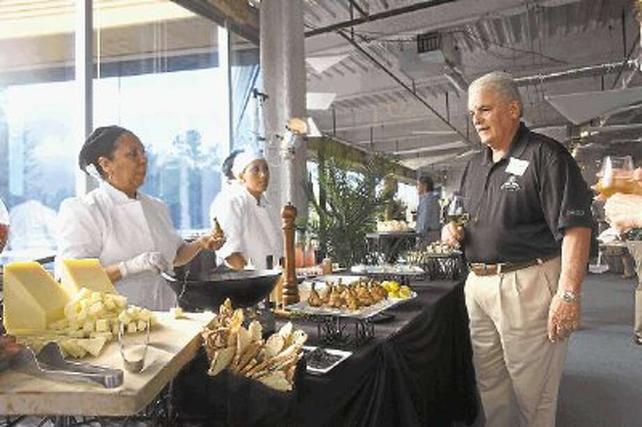 The Woodlands Township Director Mike Bass samples wine and hors d'oeuvres during a launch party for One Hughes Landing adjacent to Lake Woodlands. / @WireImgId=2643093