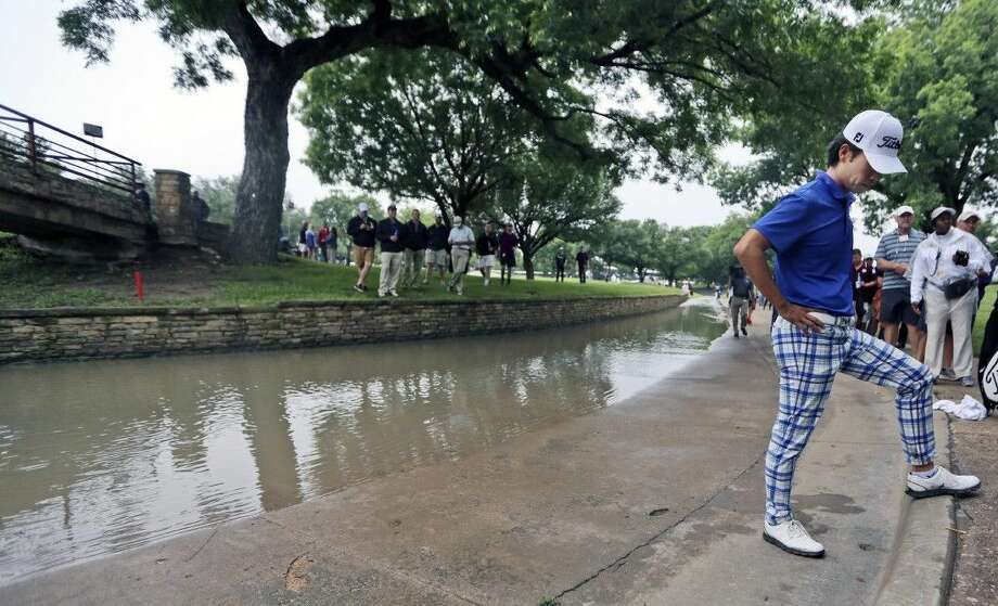 Kevin Na looks at the spot his ball landed before bouncing into a rain-swollen drainage culvert adjacent to the 18th fairway where he lost his ball during the second round of the Colonial golf tournament, Friday in Fort Worth. Photo: LM Otero