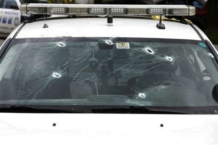 Bullet holes pierce the windshield of a police cruiser at Dallas Police headquarters after a gunman opened fire Saturday in Dallas. A man suspected of spraying the headquarters with gunfire and planting pipe bombs, early on Saturday, has been found dead in a van after a police sniper shot him, police Chief David Brown said. Photo: Ron Jenkins