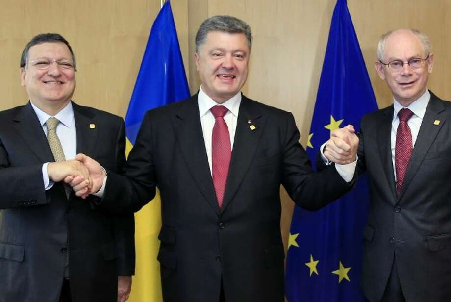 Ukraine's President Petro Poroshenko, center, poses with European Commission President Jose Manuel Barroso, left, and European Council President Herman Van Rompuy, right, during an EU Summit in Brussels on Friday.