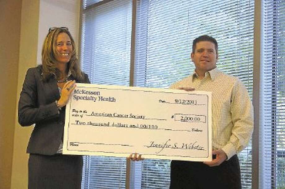 McKesson CFO Jennifer Webster hands a $2,000-check to Daryl Hayes of the American Cancer Society. The money is part of an award McKesson Specialty Health in The Woodlands received for its environmental council. / @WireImgId=2642064