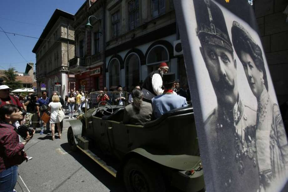 "Tourists pose for photos inside a replica of the ""Graf & Stift"" car, parked in front of a museum at the historical street corner in downtown Sarajevo, where Gavrilo Princip assassinated Austro-Hungarian heir to the throne Archduke Franz Ferdinand, in Sarajevo, on Saturday."