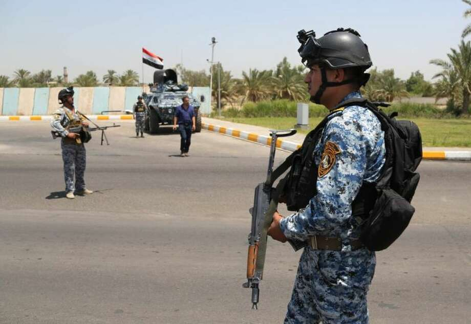 Iraqi federal policemen stand guard at a checkpoint outside of Baghdad International Airport, Iraq, Saturday.