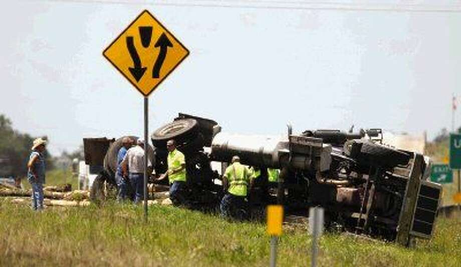 Conroe police officers work the scene of an accident involving an 18-wheeler and a truck on Loop 336 near FM 3083 Tuesday.