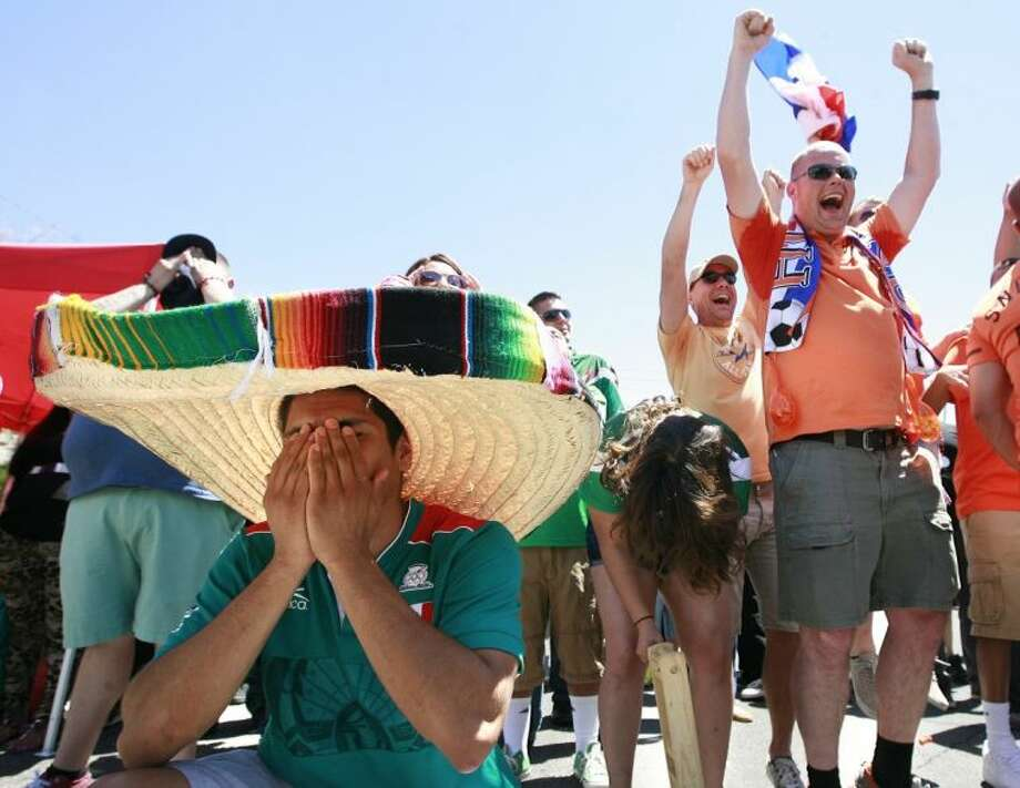 Mexico soccer fan Alex Acevedo buries his face in his hands after Holland scores their second goal of the game to beat Mexico 2-1 in their round of 16 World Cup match on Sunday. Dennis Rijsenbrij, right, of Holland celebrates the game winning goal on Robinson Street in El Paso, Texas which was closed to view the game on a giant screen. Photo: MARK LAMBIE