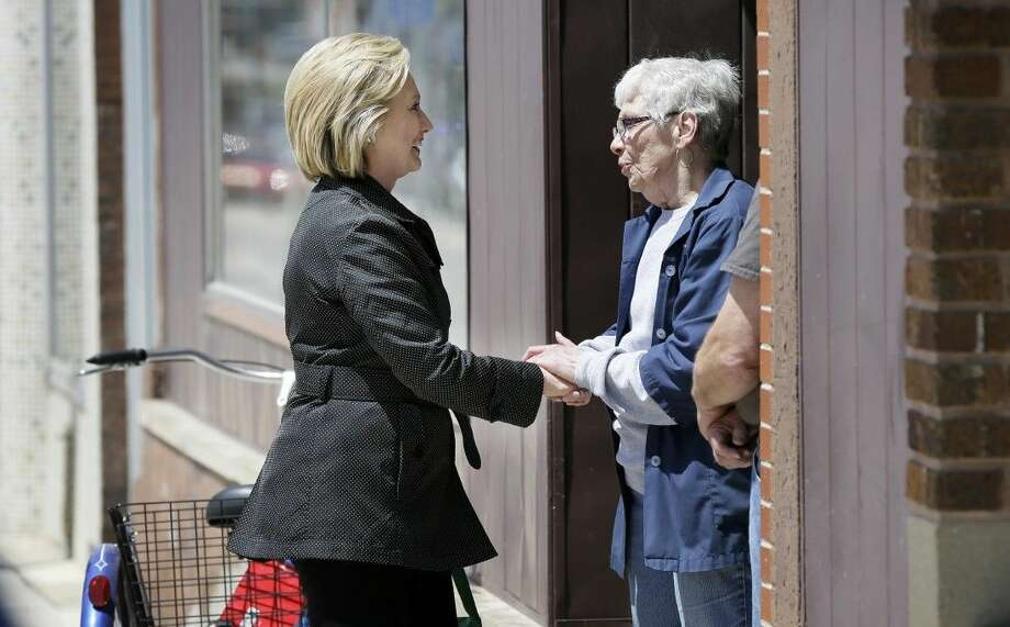 Democratic presidential candidate Hillary Rodham Clinton greets a local resident while visiting local shops on main street in Independence, Iowa, Tuesday. Photo: Charlie Neibergall