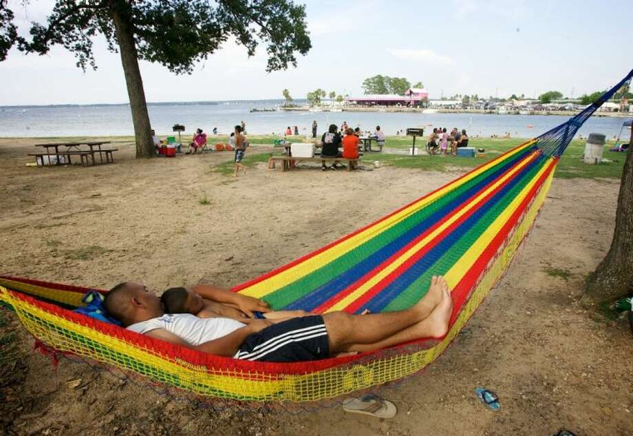 Jose Santos Ramirez sleeps on a hammock with his son Jefferson Ramirez, 5, during last year's Fourth of July at Lake Conroe Park in Conroe. The pair planned to stay to watch the fireworks over the water. Photo: Staff Photo By Eric Swist