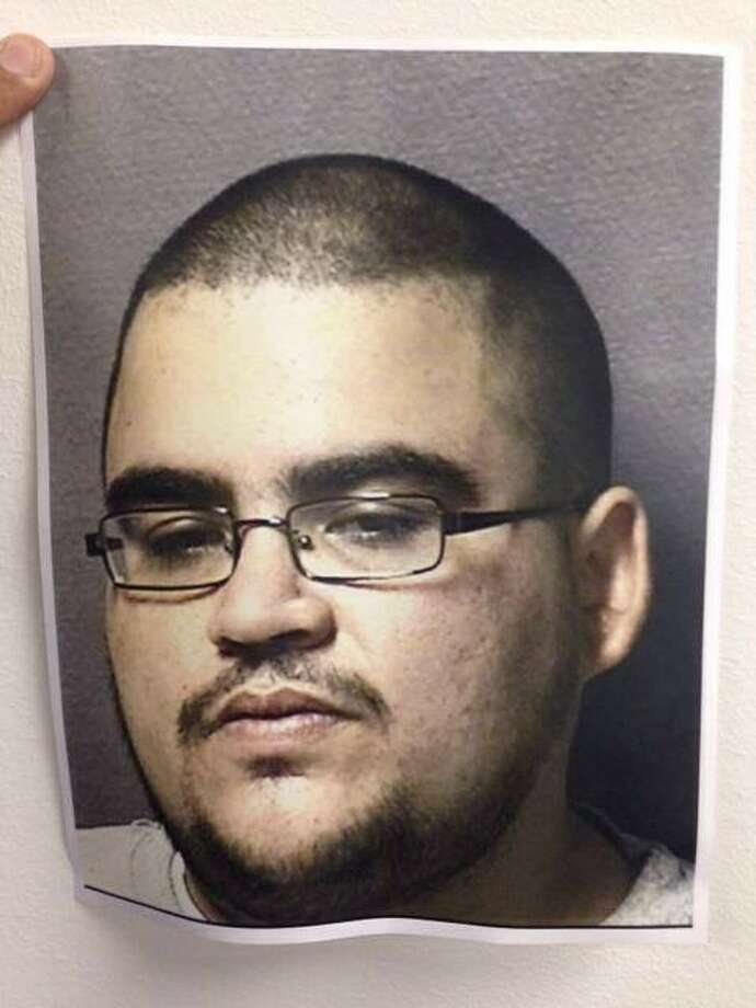 An old mugshot from a previous arrest of Efraim Carmona was shown during the press conference on Monday, June 30, 2014.