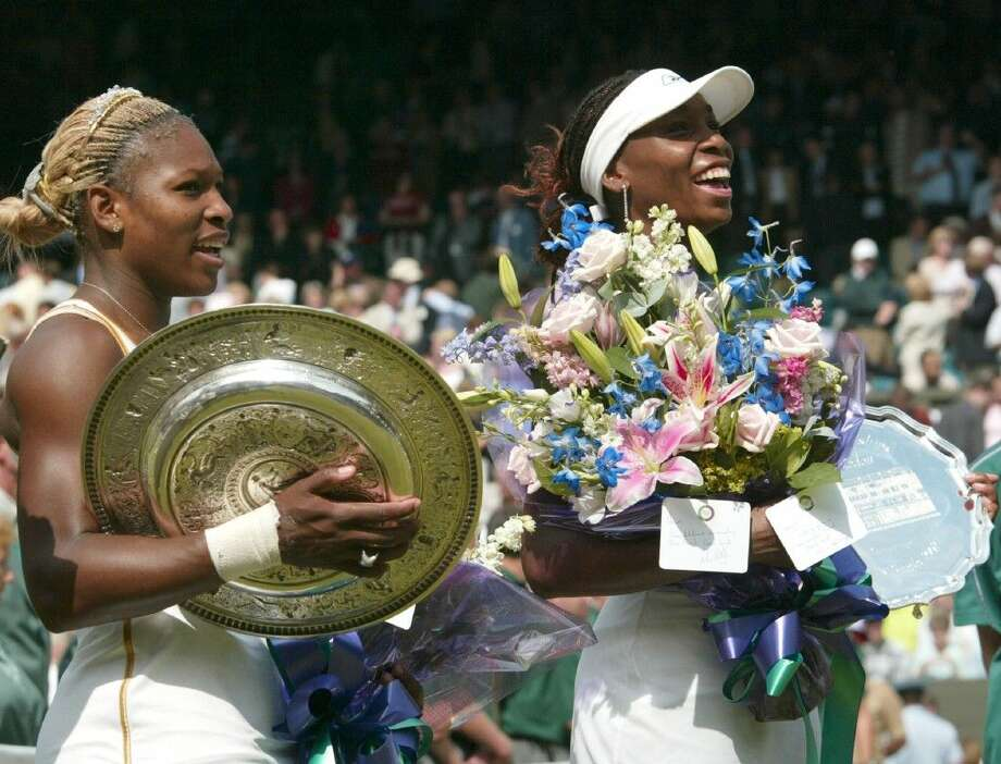 In this July 6, 2002 file photo, Serena Williams, left, holds her trophy after defeating her sister Venus, right, to win the Women's Singles final on the Centre Court at the All England Lawn Tennis Championships in Wimbledon, London. Following wins at the Australian and French Opens, Serena can become the fourth woman to win the calendar Grand Slam this year. Photo: Ted S. Warren
