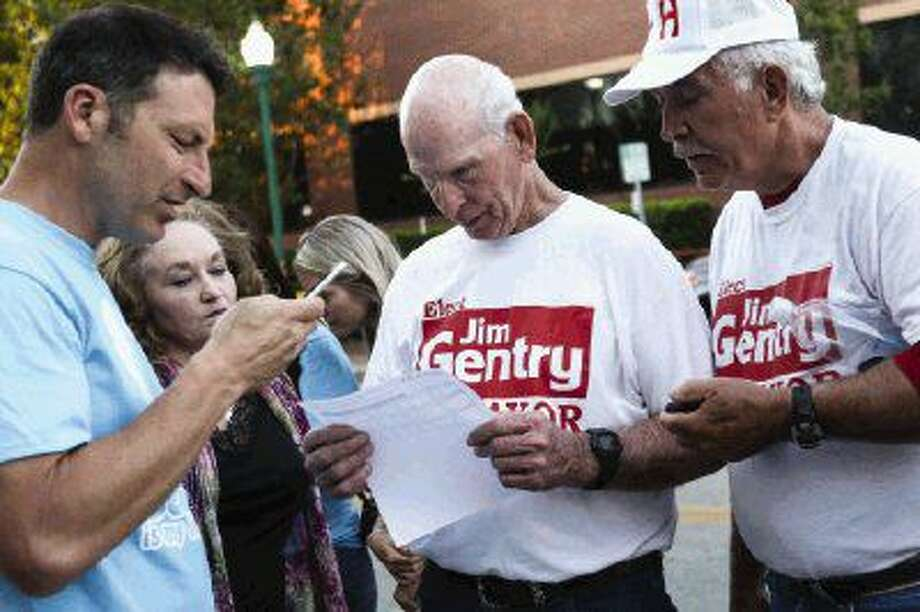 Jim Gentry, candidate for Conroe City Mayor, looks over election results with supporters on Saturday outside of Conroe Tower. Photo: Michael Minasi