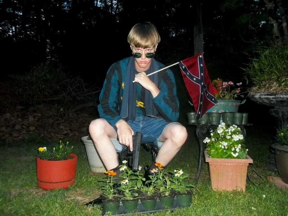 This undated file image that appeared on Lastrhodesian.com, a website being investigated by the FBI in connection with Charleston, S.C., shooting suspect Dylann Roof, shows Roof posing for a photo while holding a Confederate flag.